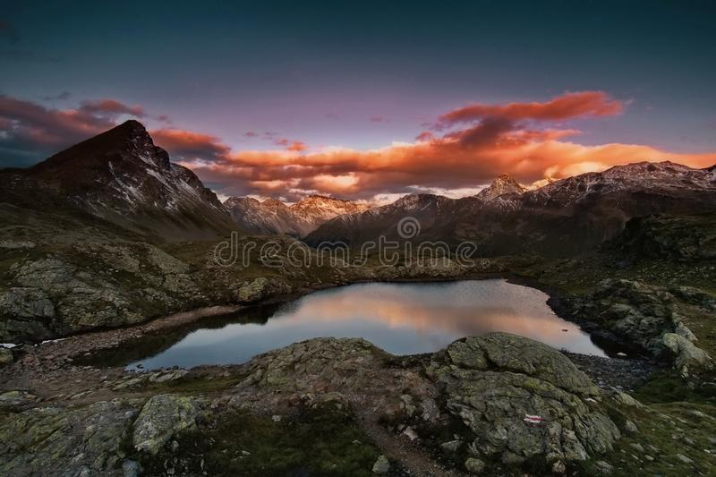 Puesta del sol en las montañas El pequeño lago, incluso en invierno, la temperatura del agua es + 30 grados El valle de géiseres foto de archivo libre de regalías