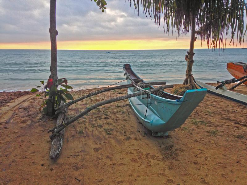 Puesta del sol en los barcos de la orilla y de pesca del Océano Índico fotografía de archivo