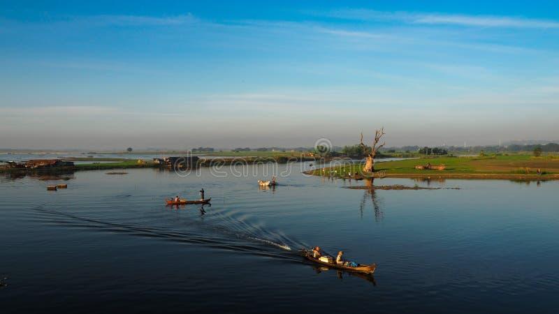 Puesta del sol en puente de U Bein con el barco Myanmar del vintage El puente de U Bein es la teca más larga imágenes de archivo libres de regalías