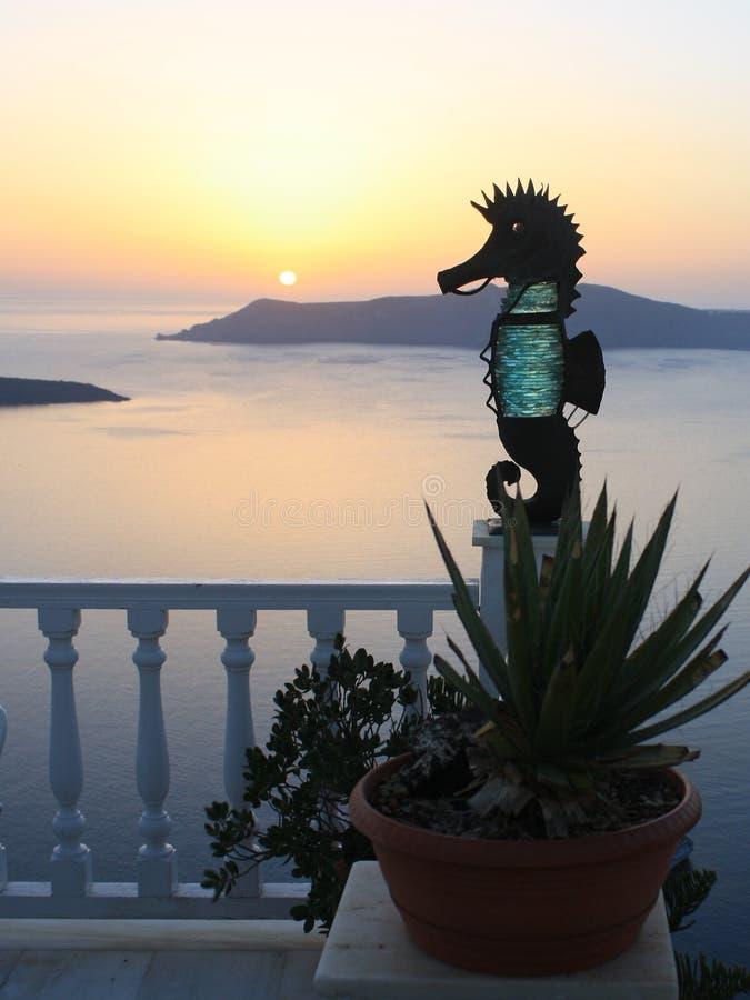 Puesta del sol en Santorini Escultura del Seahorse en la terraza de la casa Santor imagen de archivo libre de regalías