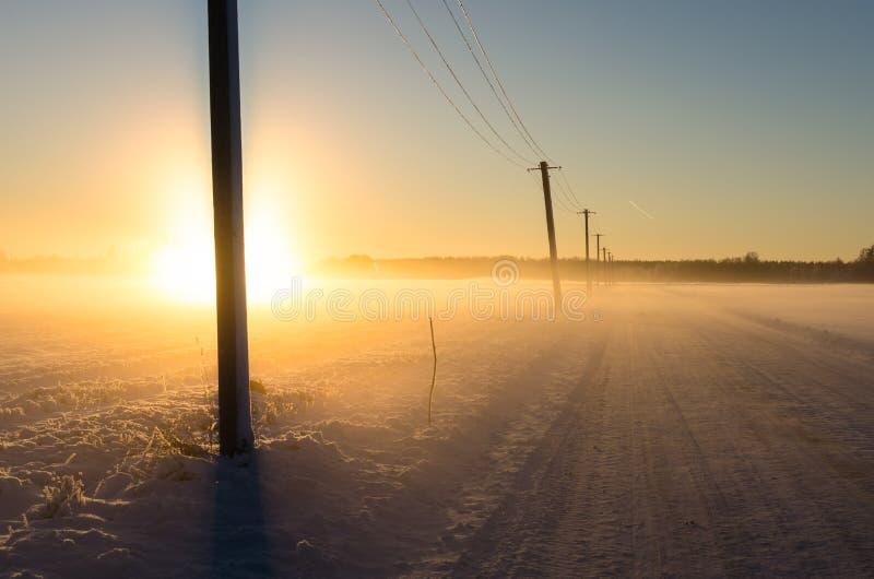 Puesta del sol en un camino de la nieve en un campo hivernal imágenes de archivo libres de regalías