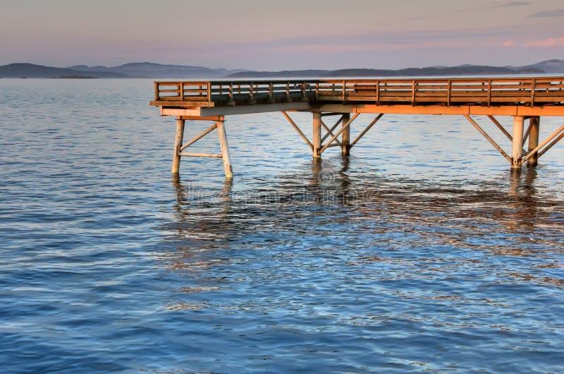 Puesta del sol en un embarcadero de madera de la pesca, Sidney, A.C. foto de archivo