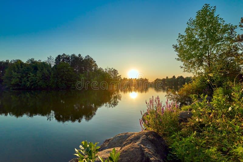 Puesta del sol en un lago con agua azul y el cielo, en la lavanda del primero plano y las piedras redondas imagen de archivo libre de regalías