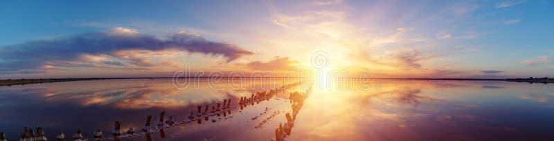 Puesta del sol en un lago de sal rosado, una mina anterior para la extracción de la sal rosada fila de las clavijas de madera dem fotos de archivo