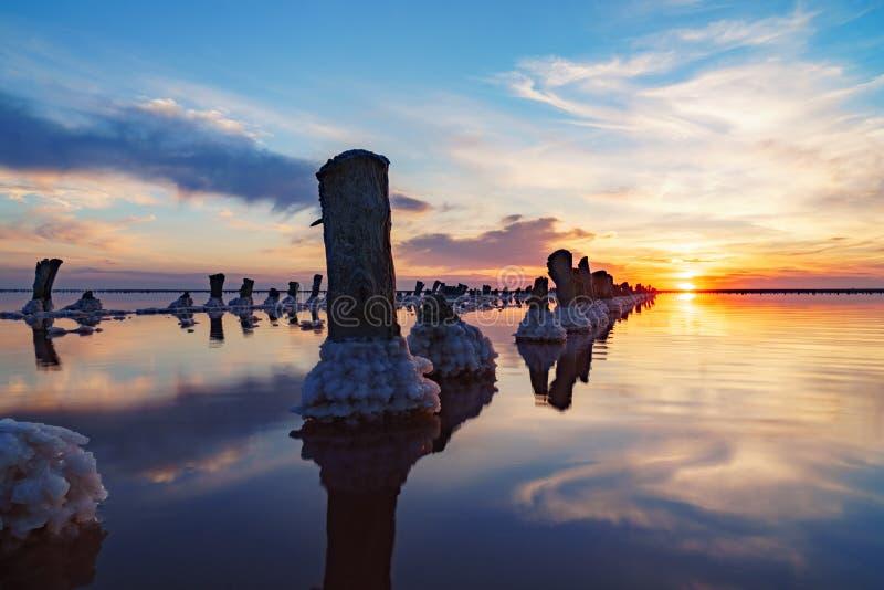 Puesta del sol en un lago de sal rosado, una mina anterior para la extracción de la sal rosada fila de las clavijas de madera dem foto de archivo