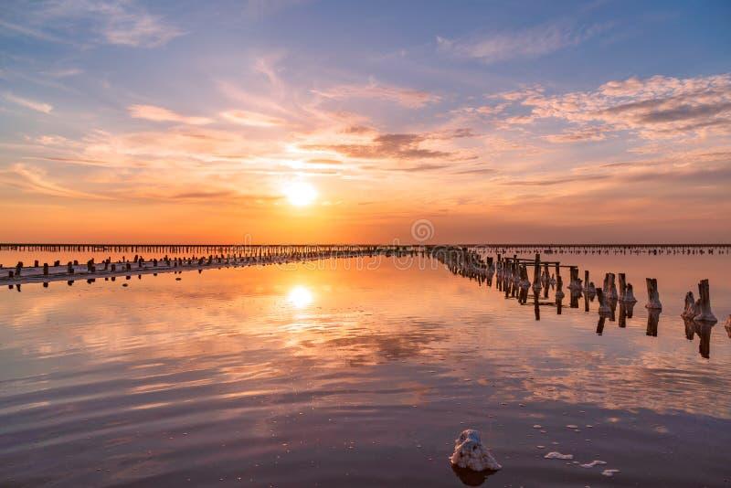 Puesta del sol en un lago de sal rosado, una mina anterior para la extracción de la sal rosada fila de las clavijas de madera dem fotos de archivo libres de regalías