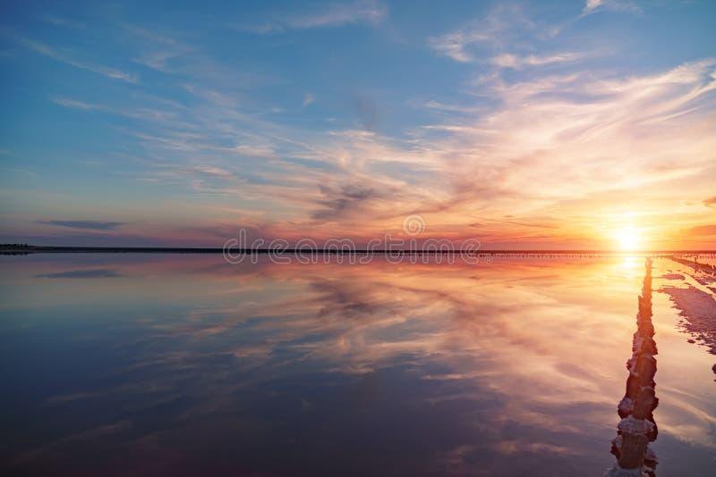 Puesta del sol en un lago de sal rosado, una mina anterior para la extracción de la sal rosada fila de las clavijas de madera dem imágenes de archivo libres de regalías