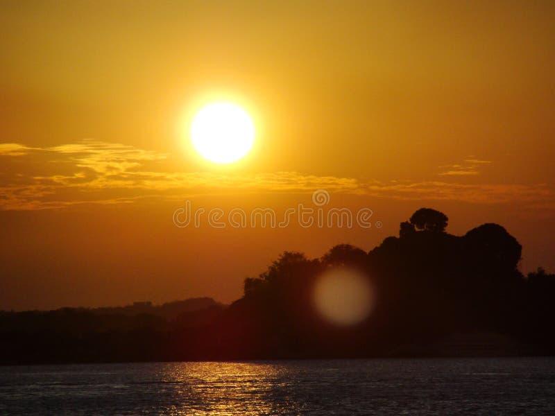 Puesta del sol en un lago del océano del río con un rayo de la luz del sol que refleja en el agua durante la hora de oro fotos de archivo libres de regalías
