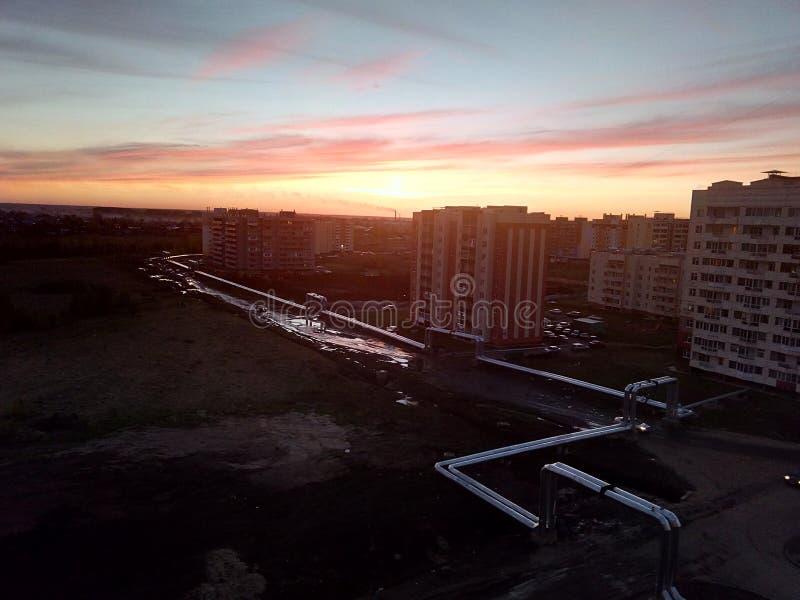 puesta del sol en una pequeña ciudad ordinaria foto de archivo