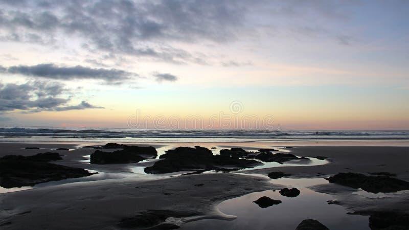 Puesta del sol en una playa aislada exótica en Costa Rica, rocas volcánicas y playa fotografía de archivo