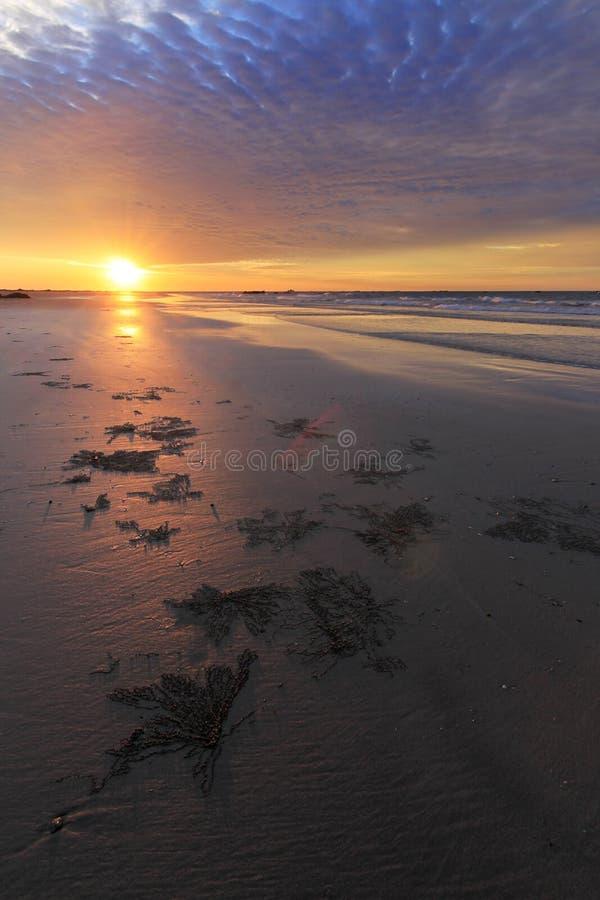 Puesta del sol en una playa arenosa fotos de archivo