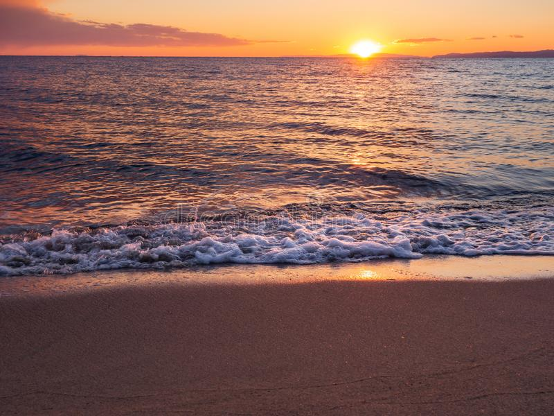 Puesta del sol en una playa arenosa vac?a hermosa - ondas espumosas fotografía de archivo