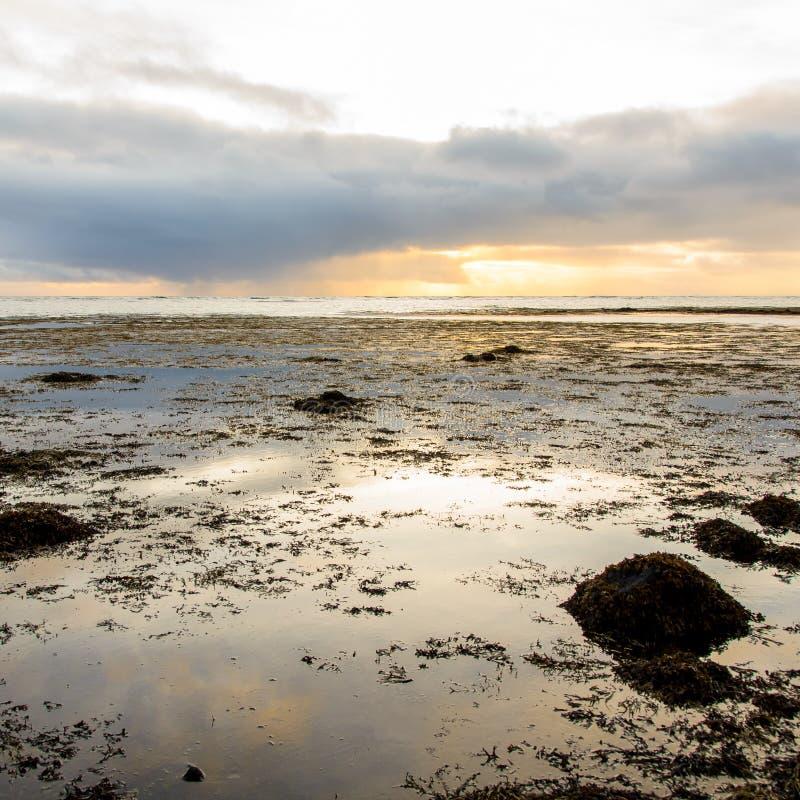 Puesta del sol en una playa negra de la arena fotografía de archivo