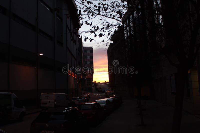 puesta del sol entre los coches fotografía de archivo