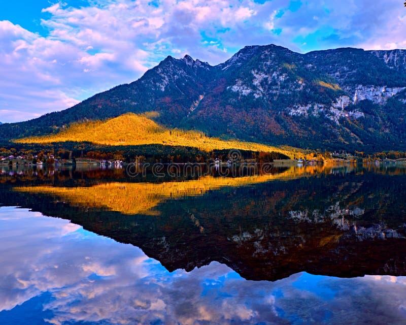Puesta del sol escénica hermosa en el lago austríaco de las montañas Casas rurales del viejo vintage y casas barco de madera en l foto de archivo