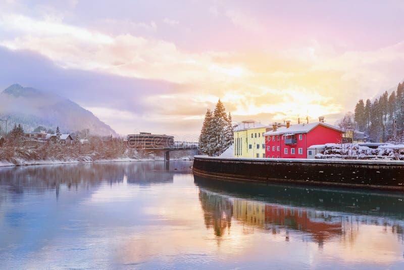 Puesta del sol escénica hermosa sobre mesón del río en la ciudad de Kufstein con los árboles cubiertos con nieve y montañas en fo fotos de archivo
