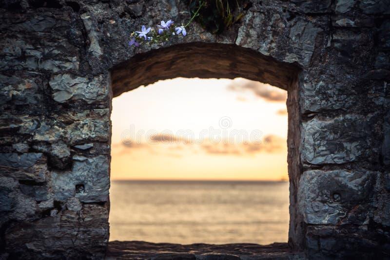 Puesta del sol escénica sobre el mar a través de la ventana de ruinas viejas con la opinión dramática del cielo y de perspectiva  imagen de archivo