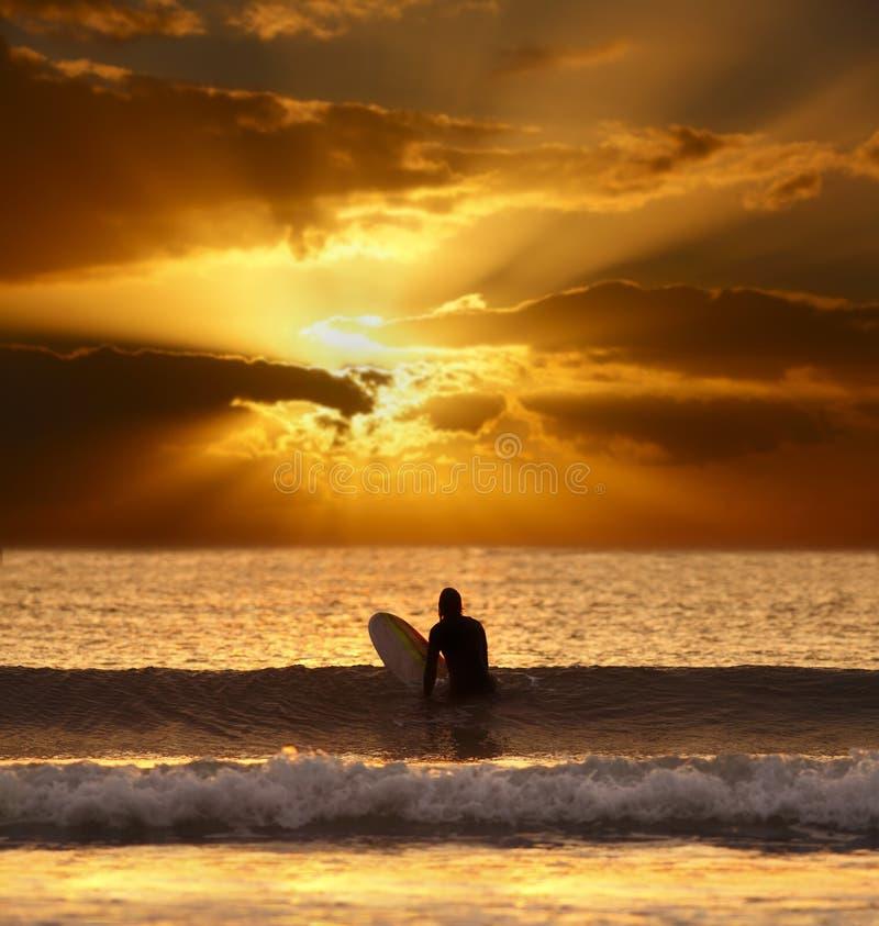 Puesta del sol espectacular con la persona que practica surf imagen de archivo libre de regalías