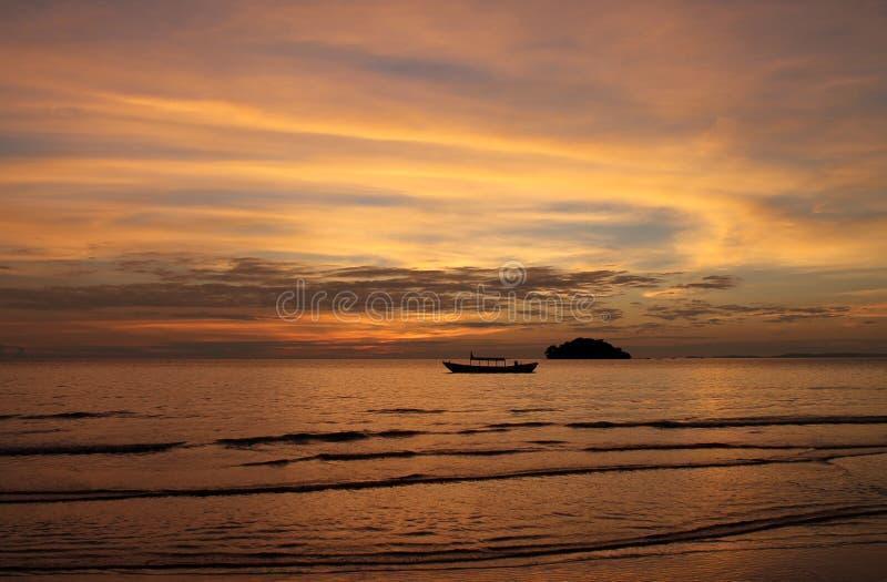 Puesta del sol espectacular sobre el barco y el mar de la cola larga fotografía de archivo