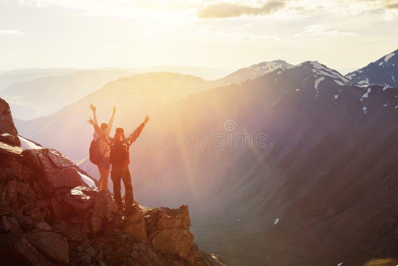 Puesta del sol feliz de dos saludos de los turistas con las manos aumentadas imágenes de archivo libres de regalías
