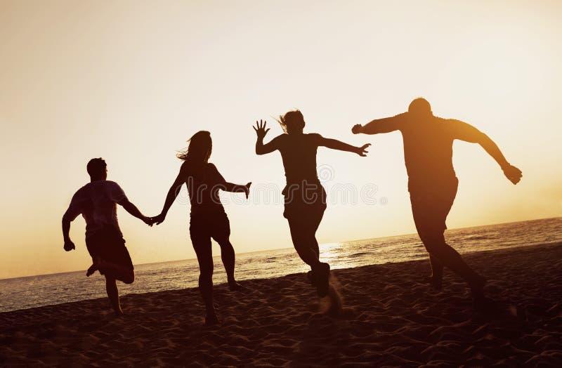 Puesta del sol del funcionamiento de la playa de la gente de los amigos del grupo de las siluetas imagen de archivo
