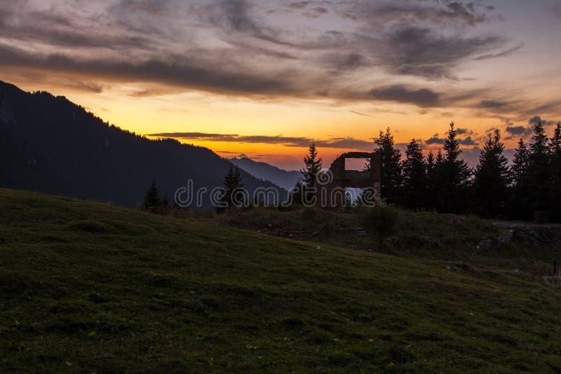 Puesta del sol hecha en el otoño cerca de la ruina de una choza de la montaña imagenes de archivo