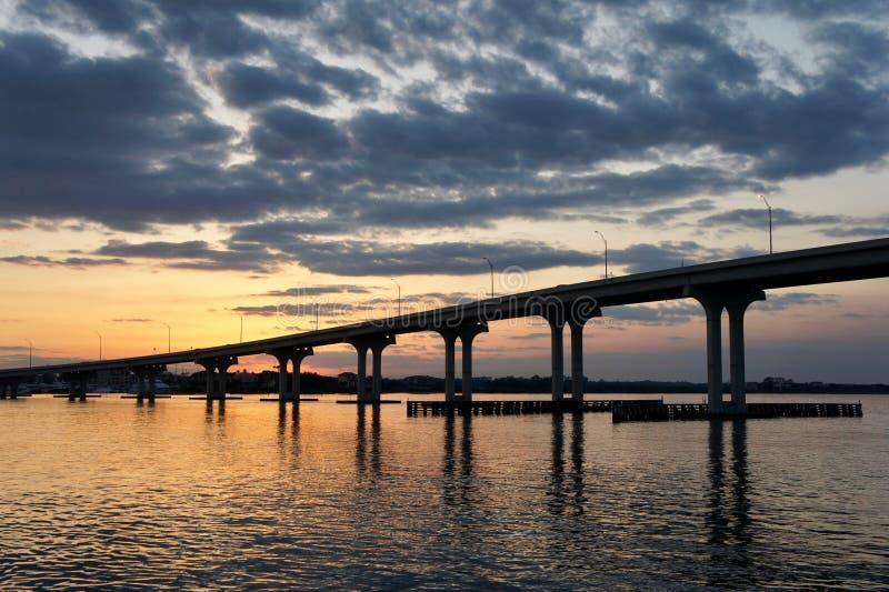 Puesta del sol hermosa con un puente y un agua fotos de archivo