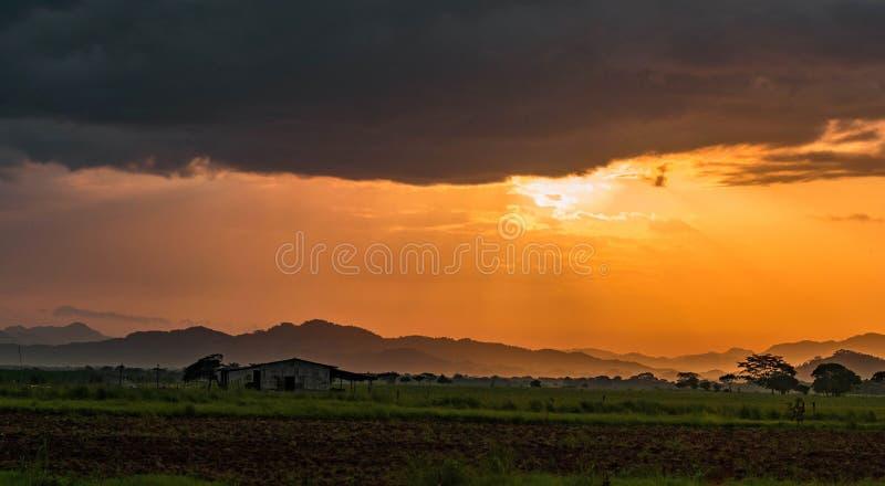 Puesta del sol hermosa con una casa vieja y rayos ligeros anaranjados fotografía de archivo
