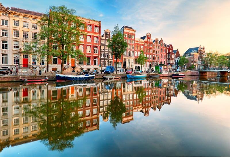 Puesta del sol hermosa de Amsterdam Casas holandesas viejas típicas en el puente y los canales en la primavera, Países Bajos foto de archivo libre de regalías