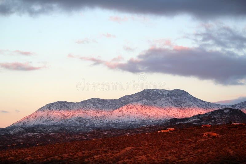 Puesta del sol hermosa del invierno con las montañas nevadas de Santa Catalina Pusch Ridge en Tucson, Arizona foto de archivo