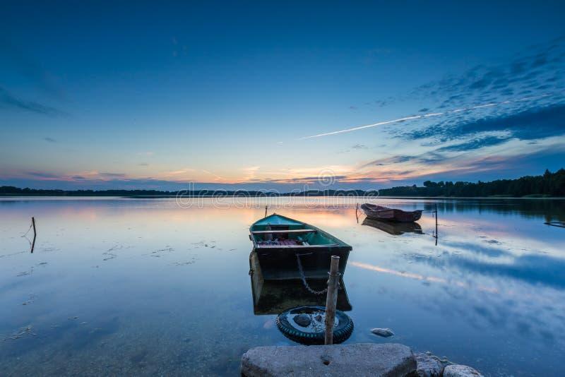 Puesta del sol hermosa del lago con los barcos del pescador fotos de archivo libres de regalías