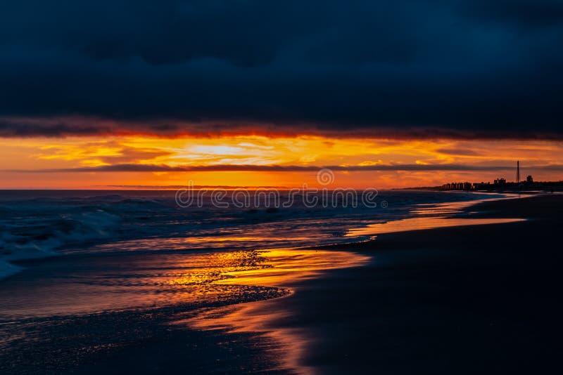 Puesta del sol hermosa en el borde del mar El cielo y la arena se cubren con reflexiones de oro imagenes de archivo