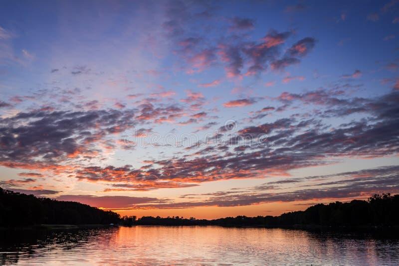 Puesta del sol hermosa en el lago del verano con las nubes dinámicas imagen de archivo libre de regalías