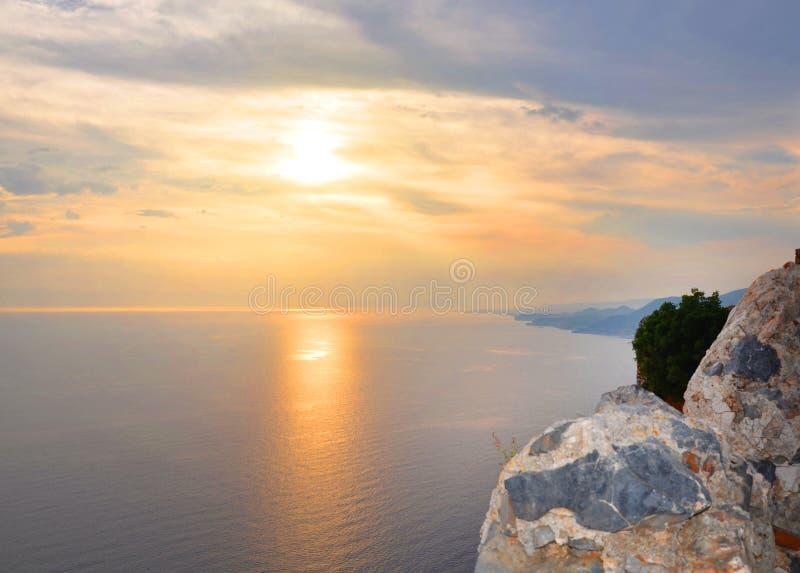 Puesta del sol hermosa en el mar con el cielo nublado, nubes grises y anaranjadas, trayectoria de oro en el mar, el concepto de v foto de archivo