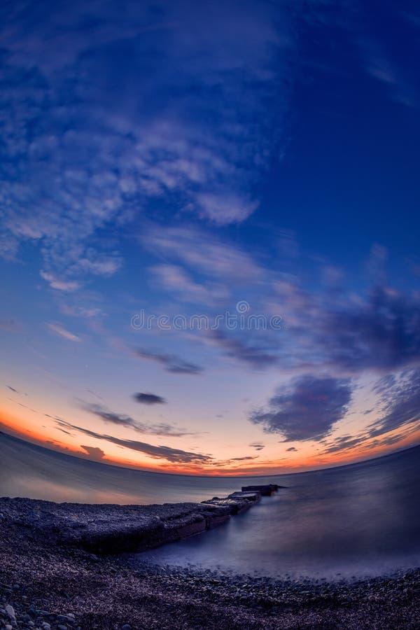 Puesta del sol hermosa en la orilla de mar con un pontón de piedra en las FO fotografía de archivo
