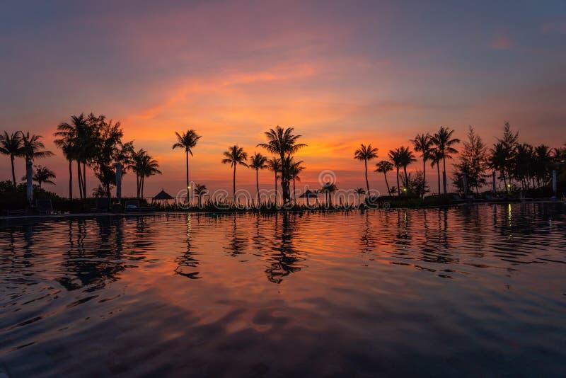 Puesta del sol hermosa en la piscina en centro turístico de lujo fotografía de archivo