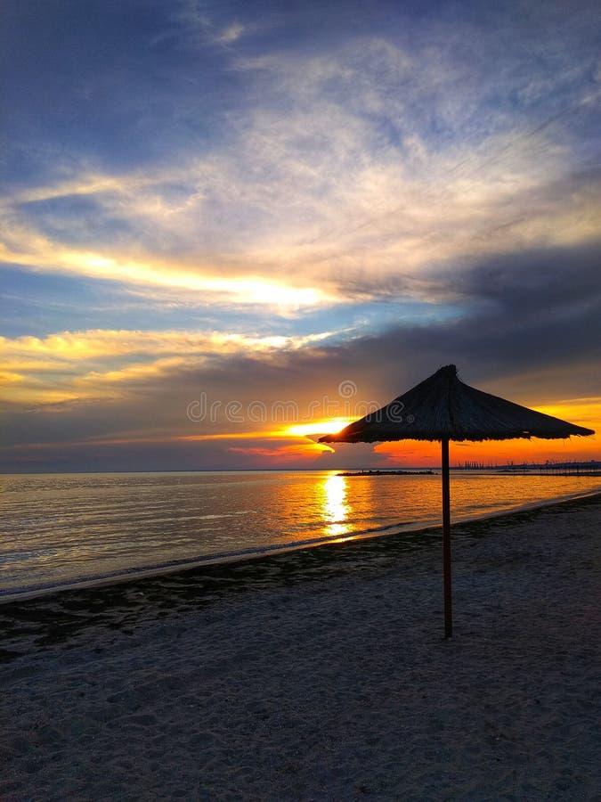 Puesta del sol hermosa en la playa arenosa Paraguas por el mar, calma, fondo natural hermoso de la paja fotos de archivo libres de regalías