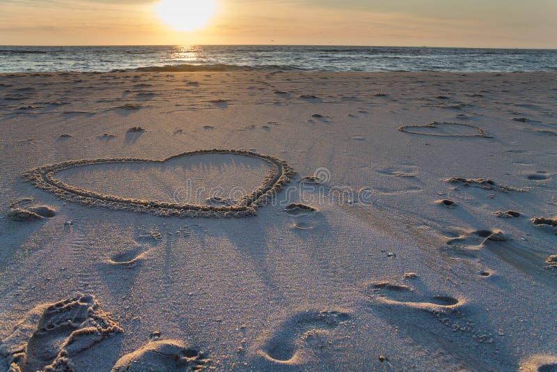 Puesta del sol hermosa en la playa con las pilas y los dibujos de madera de los corazones en la arena fotos de archivo libres de regalías