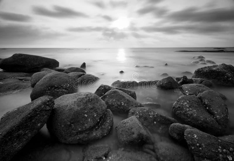 Puesta del sol hermosa en la playa de piedra en blanco y negro fotos de archivo