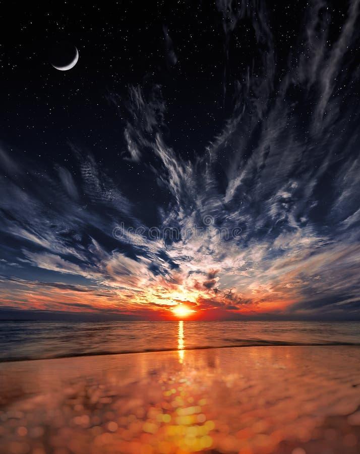 Puesta del sol hermosa en la playa, las estrellas y la luna en el cielo fotografía de archivo