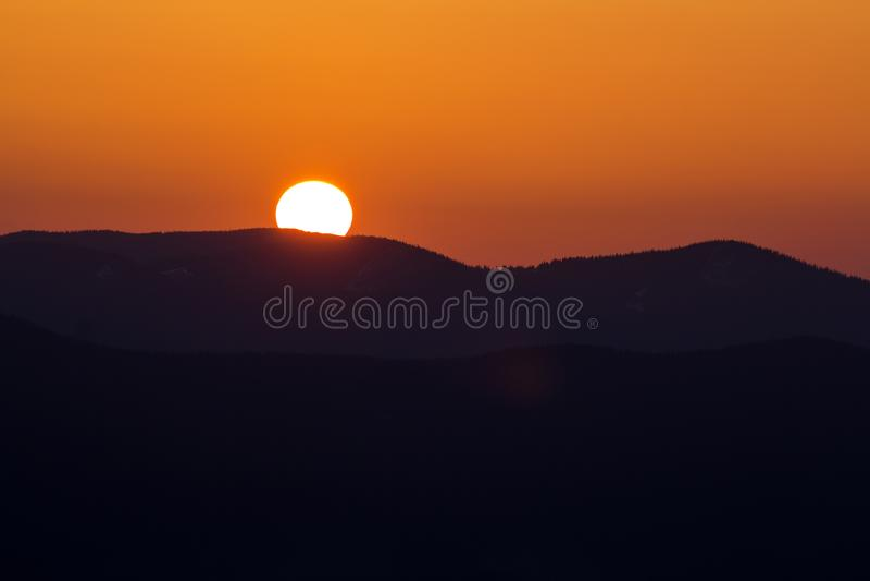 Puesta del sol hermosa en montañas Opinión amplia del panorama del sol blanco brillante grande en cielo anaranjado dramático sobr fotografía de archivo