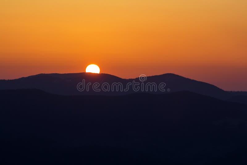 Puesta del sol hermosa en monta?as Opini?n amplia del panorama del sol blanco brillante grande en cielo anaranjado dram?tico sobr imágenes de archivo libres de regalías