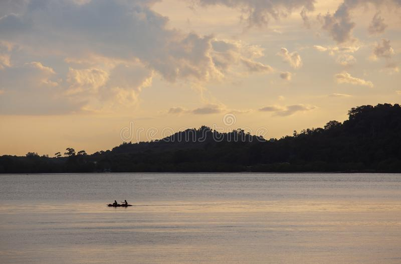 Puesta del sol hermosa kayaking en un pacífico en la playa tropical en Tailandia imagen de archivo libre de regalías