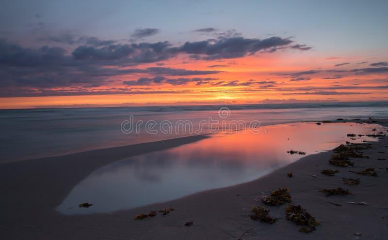 Puesta del sol hermosa del mar Báltico con reflexiones en el agua foto de archivo