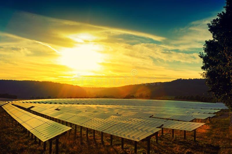 Puesta del sol hermosa sobre campo de energía solar imagenes de archivo