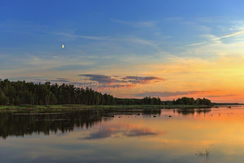 Puesta del sol hermosa sobre el bosque y el lago foto de archivo libre de regalías