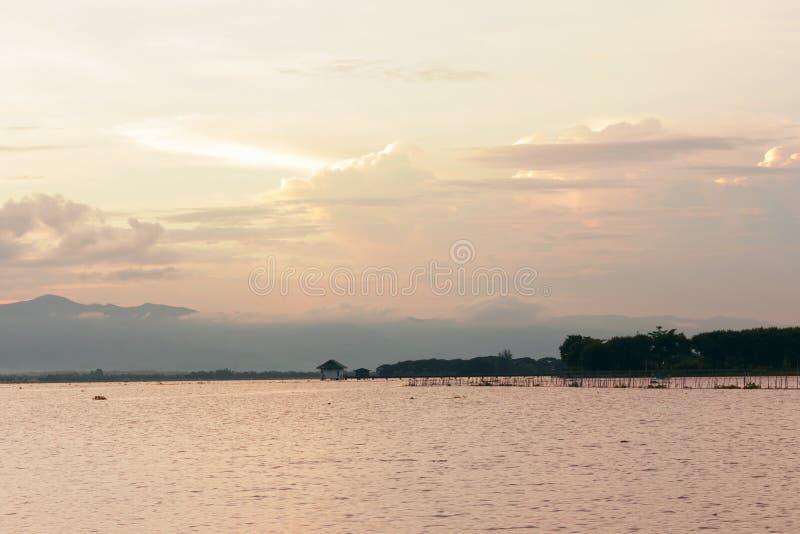 Puesta del sol hermosa sobre el lago tranquilo con el cielo nublado en Tailandia fotografía de archivo libre de regalías
