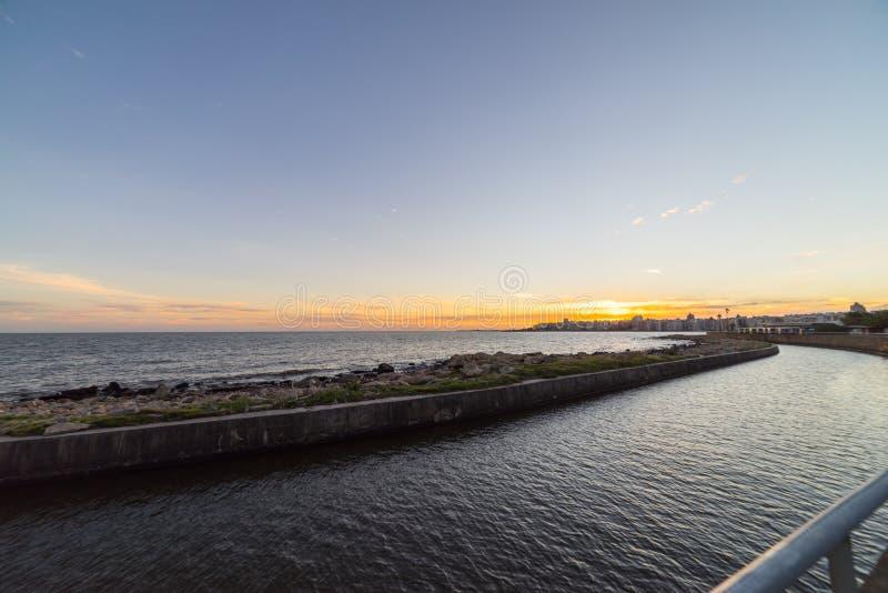 Puesta del sol hermosa sobre el paseo marítimo y la playa de Montevideo, Uruguay fotografía de archivo libre de regalías