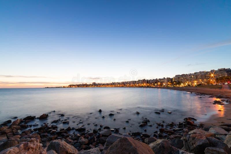Puesta del sol hermosa sobre el paseo marítimo y la playa de Montevideo, Uruguay imagen de archivo libre de regalías