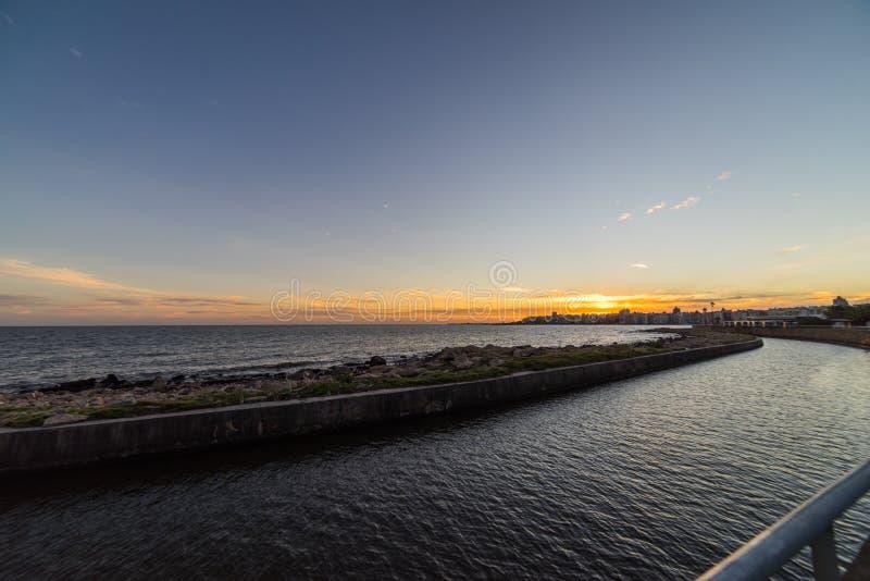 Puesta del sol hermosa sobre el paseo marítimo y la playa de Montevideo, Uruguay fotos de archivo